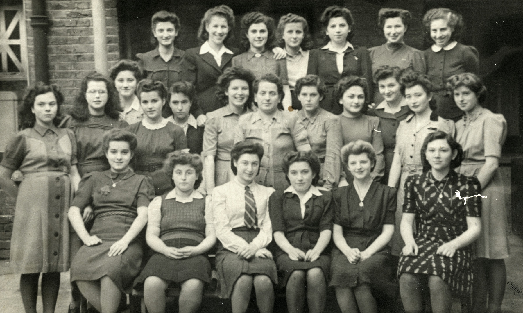 A group photograph at the Cazenova Road Hostel in London England.   The photograph was taken either during war time or during the post war. Gerda Beruh wears a tie in front with her sister Sonja Beruh, who is behind her with curly hair.   Pictured from left to right and top to bottom; Gertie Rosner, Rosie Feingold, Pia, Lottie Shershevsky, Adela Redner, Yehudit, Ilse Schechler, Ruth Freund, Gertie Wolfgang Urman, Paula, Erica Figdor, Ruth Freund, Sonja Beruh, Dora Margolies (Matron of the House), unnamed, Theo, unnamed, Regina, unnamed, Ava Figdor Levy, unnamed, Gerda Beruh, unnamed, unnamed, unnamed.