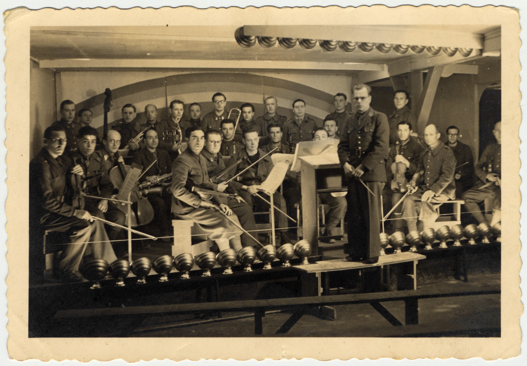 Ferdinand Carrion, a Belgian musician and prisoner-of-war, conducts the prisoner's orchestra in Stalag VIII-A.  Max Beker, a Jewish POW from Vilna, is the concertmaster.