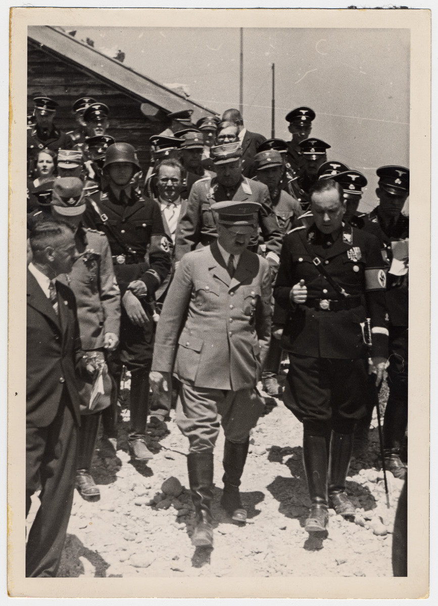 Adolph Hitler walks and converses with a Nazi official in the center of a large crowd of other Nazi soldiers.  Ernst Roehm is directly behind him and [perhaps Alfred Rosenberg] are walking next to Hitler.