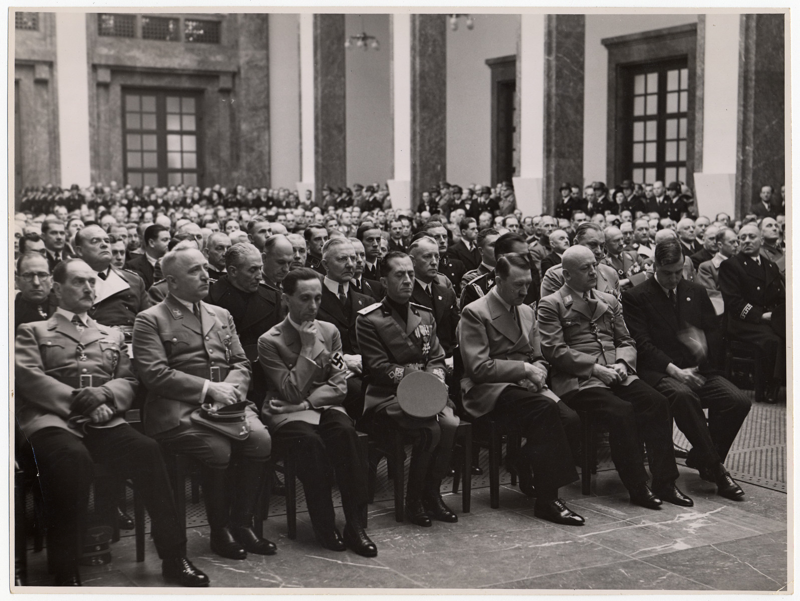 Adolf Hitler and other Nazi officials gather in a large room lto listen to a speaker.  Front tow: Robert Ley (second from the left), Joseph Goebbels (third from the left).  Behind him to the right in the second row is Hjalmar Schacht and Hermann Goering is seated in the second row on the aisle.