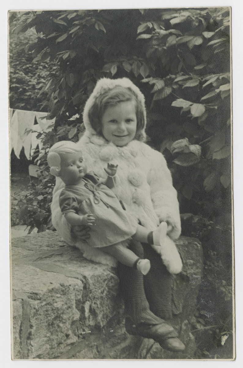 Mania Klajnburd sits outside dressed in a fur coat and matching hat clutching her doll in the Lechfeld displaced persons camp.