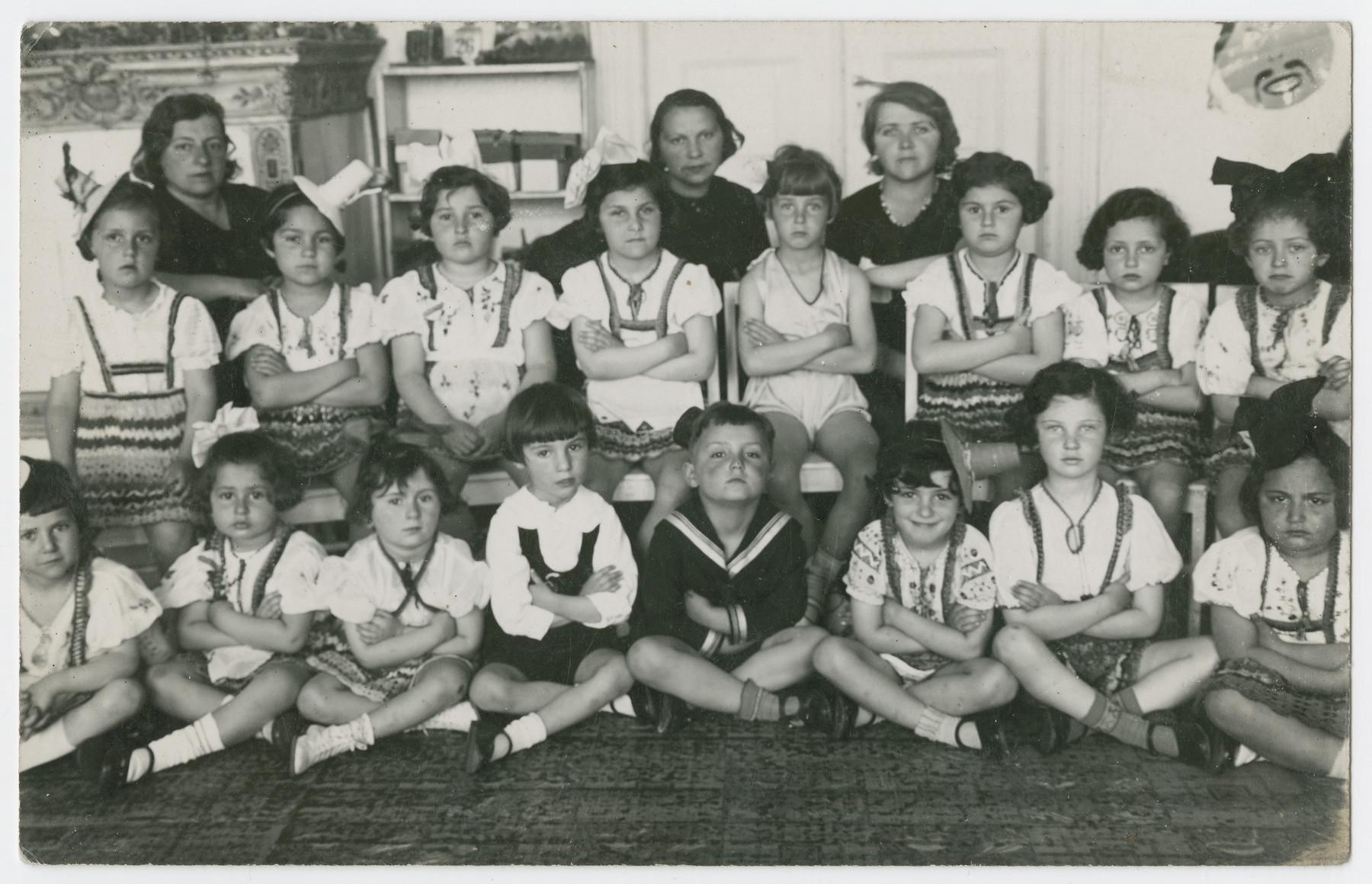 A class portrait taken inside [a schoolroom].