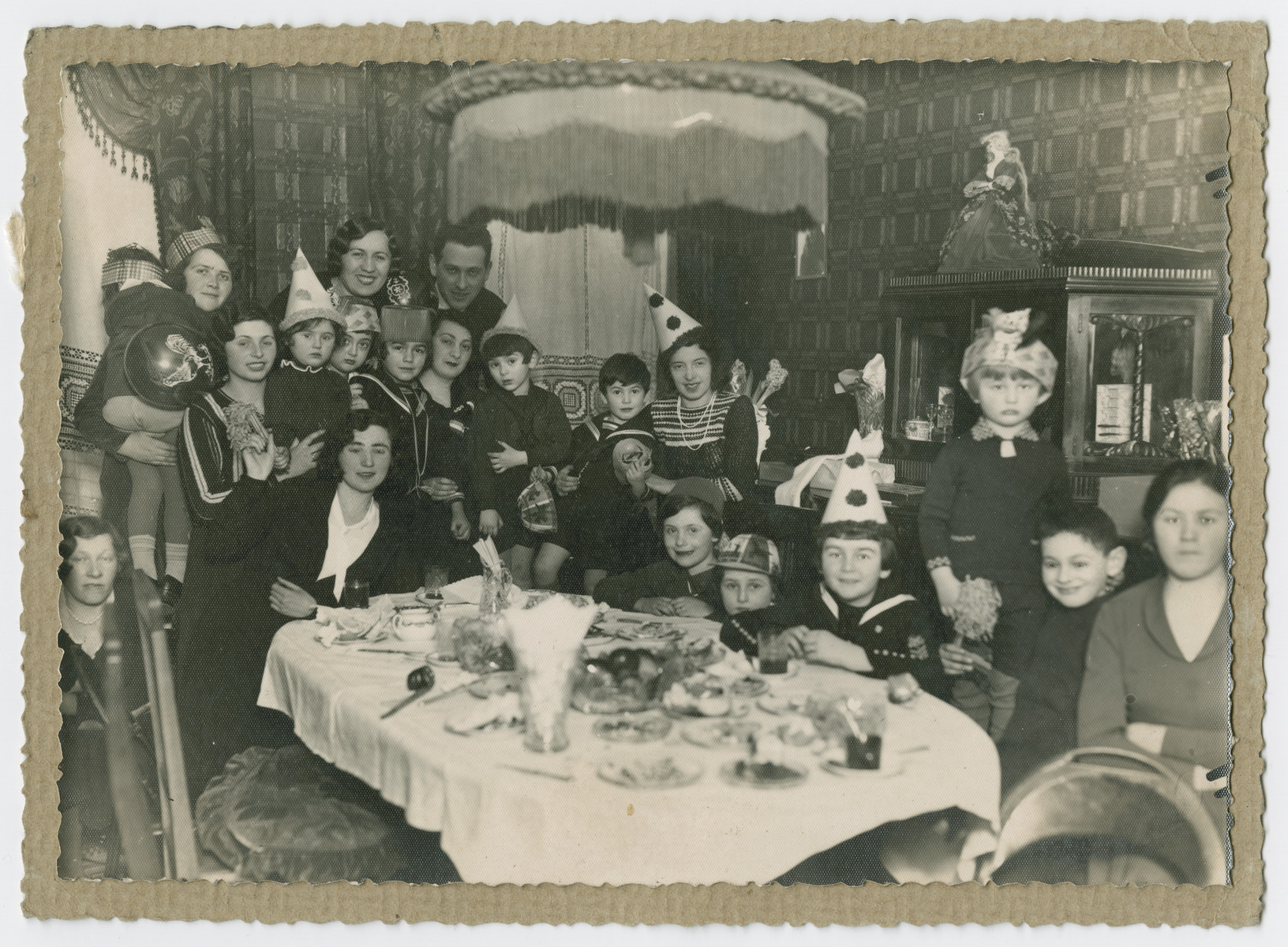 Children and women gather by a festive table for a celebration [possibly a birthday].