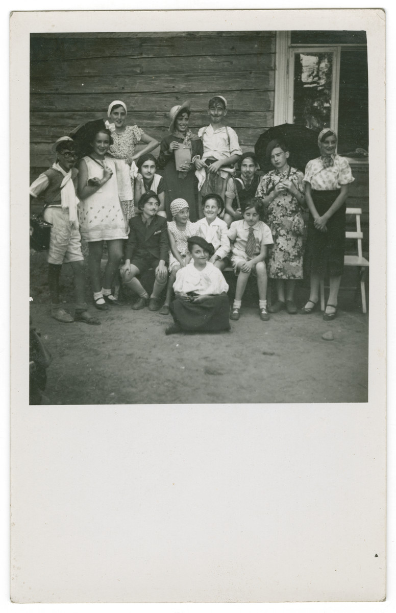 Group portrait of children, some in costume, outside  a building.