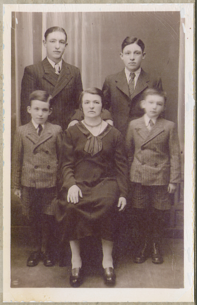 Studio portrait of the Press family before the war.  Sonja Press is flanked by her two twin sons, Mayer and Welrel.  Behind them are Gershon and Berl.