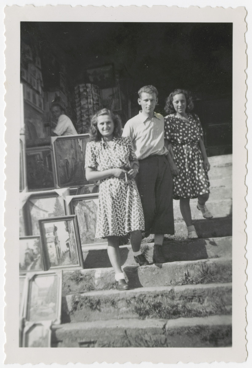 Three young people pose next to an outdoor art display.  Eva Weinberger is pictured in the front left.