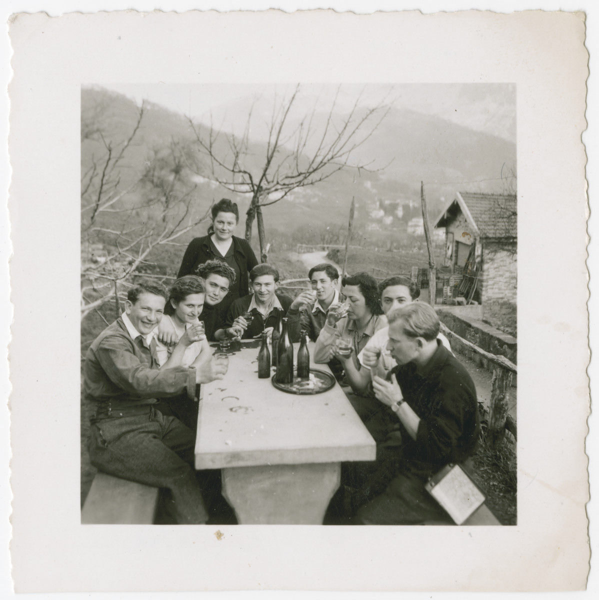A group of young people enjoys a drink while on an excursion through the Swiss countryside.  Eva Weinberger is pictured seated at the table, second from the left.  Shlomo is next to her in front.  Berta Rubinstzajn is third in on the right sipping water.
