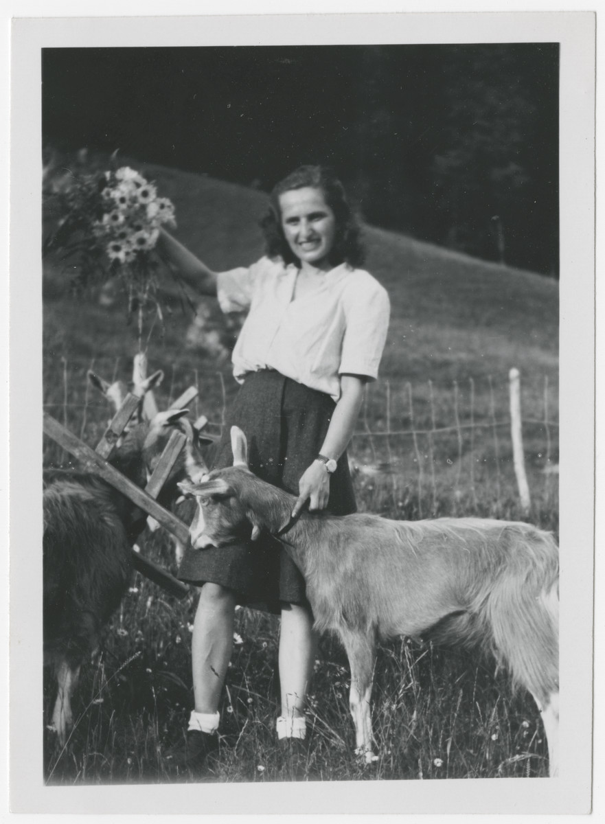 Close-up portrait of Eva Weinberger holding a bouquet of wild-flowers in one hand and a goat's collar with the other.