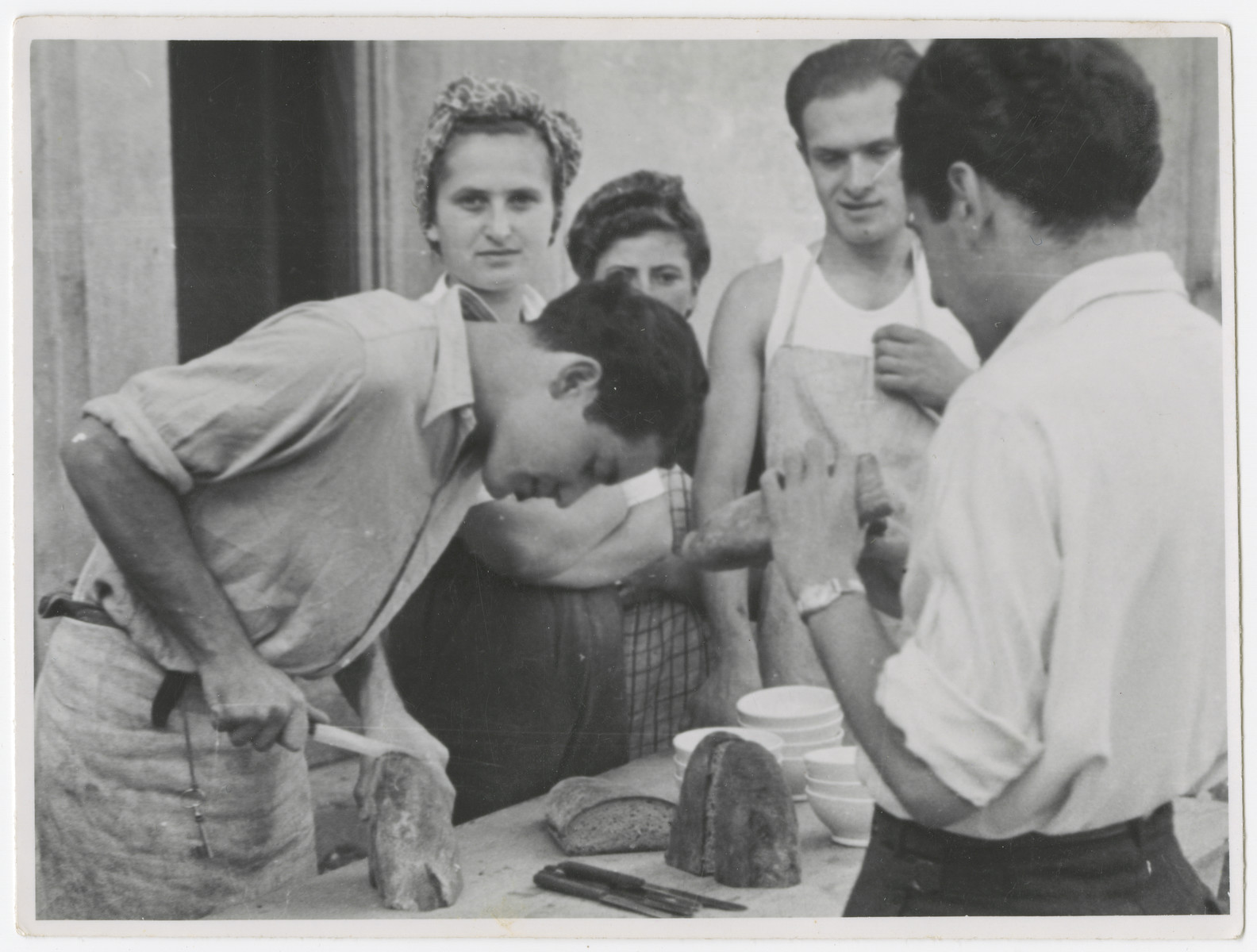 Zionist youth, some who came to Switzerland on the Kasztner transport, prepare a meal in a kibbutz hachshara near Bern.  Eva Weinberger is pictured second from the left facing the camera.  Berta Rubinsztajn is next to her partially obscured.