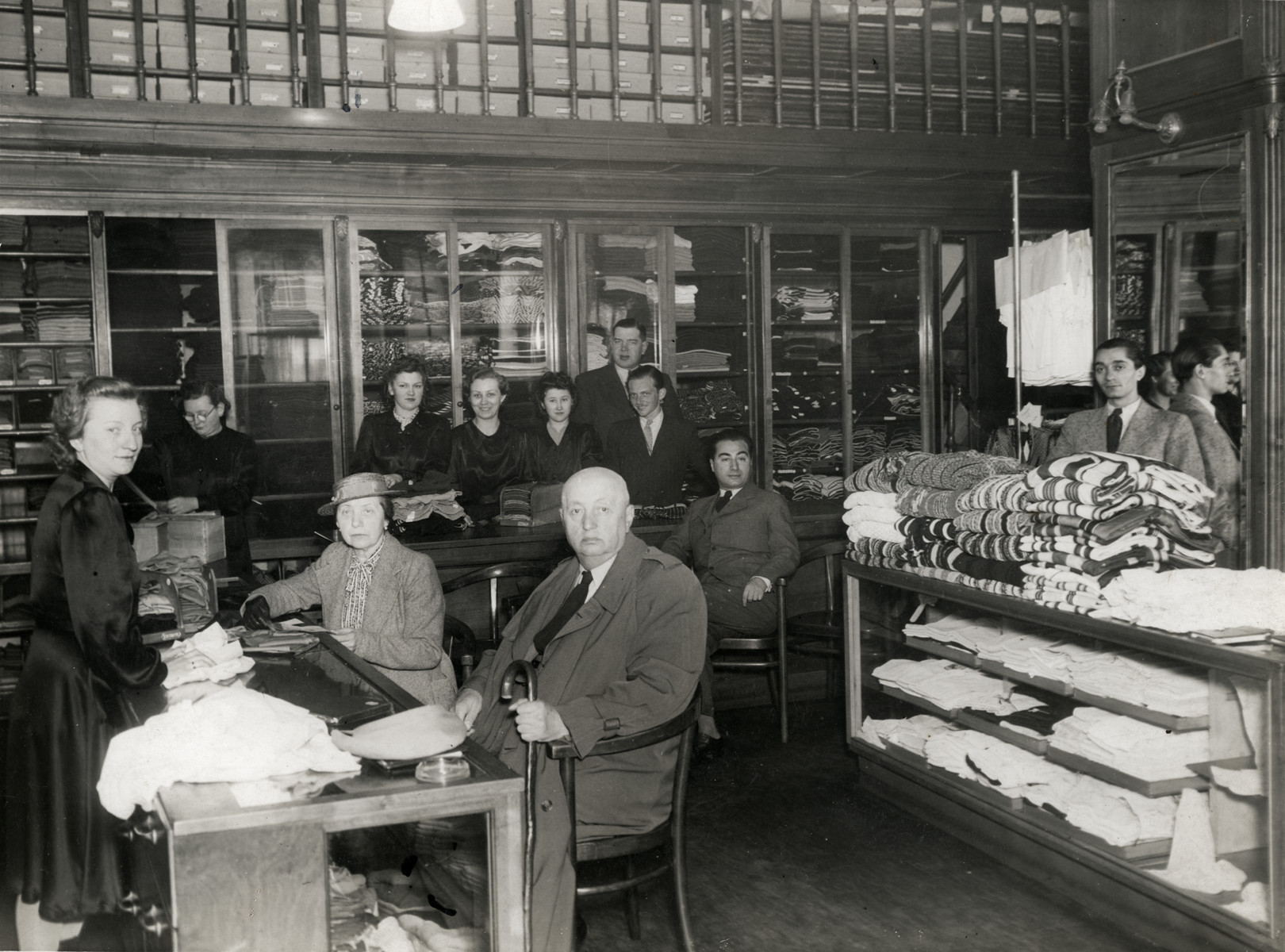 The staff of the Somlo knit wear store in Budapest, Hungary assists a Polish prince and his wife who came to purchase goods.
