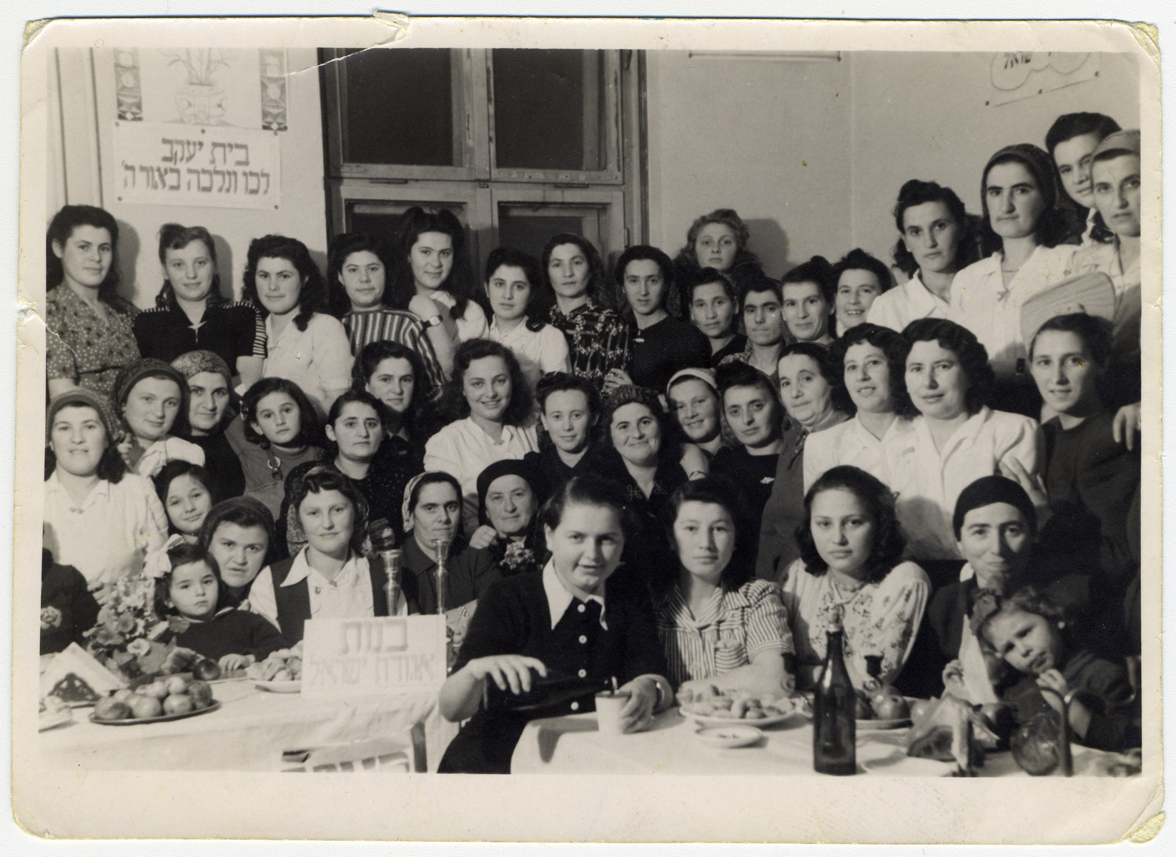 Girls from Bnot Agudat Yisrael and Beit Yaakov hold a celebration in the Bad Gastein displaced persons camp.  Pictured are Esther Ass second from the right first row.  Her sister Itka is pictured in the middle of the middle row in a light colored blouse. Also pictured is Hinde Goldberg (fifth from the right, middle row) and to her right is Yente Gelkop, and Chava Joskovitch.  Lola Schwartz nee Fried, is in the back center, with her shadow on the wall. Her sister, Magda (Matel) Gruen nee Fried,  is in the second row left, right under the woman in the printed dress.