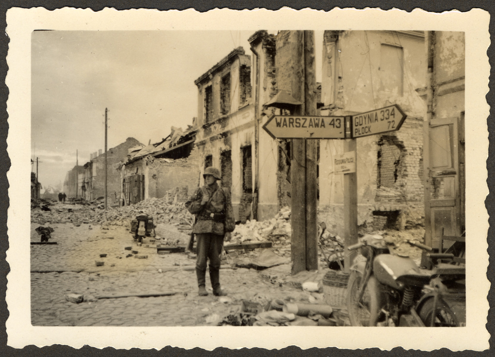 "A German soldier stands in the ruins of the city center in Zakroczym, Poland, near Warsaw.   Original German caption reads: ""City Midpoint in Zakroczym."""