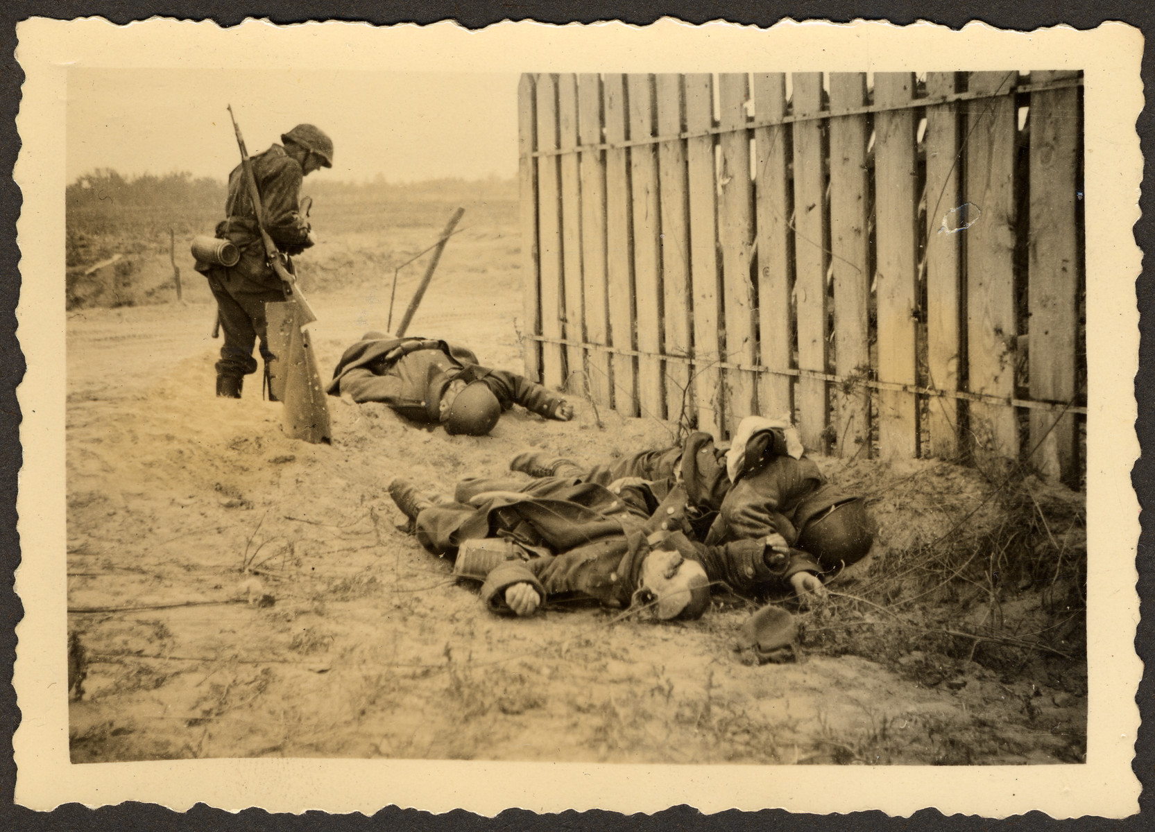 """A German soldier looks down upon the bodies of fallen Polish soldiers during the Invasion of Poland.  Original German caption read: """"Picture of the edge of the street, Poland goes along with us completely."""""""