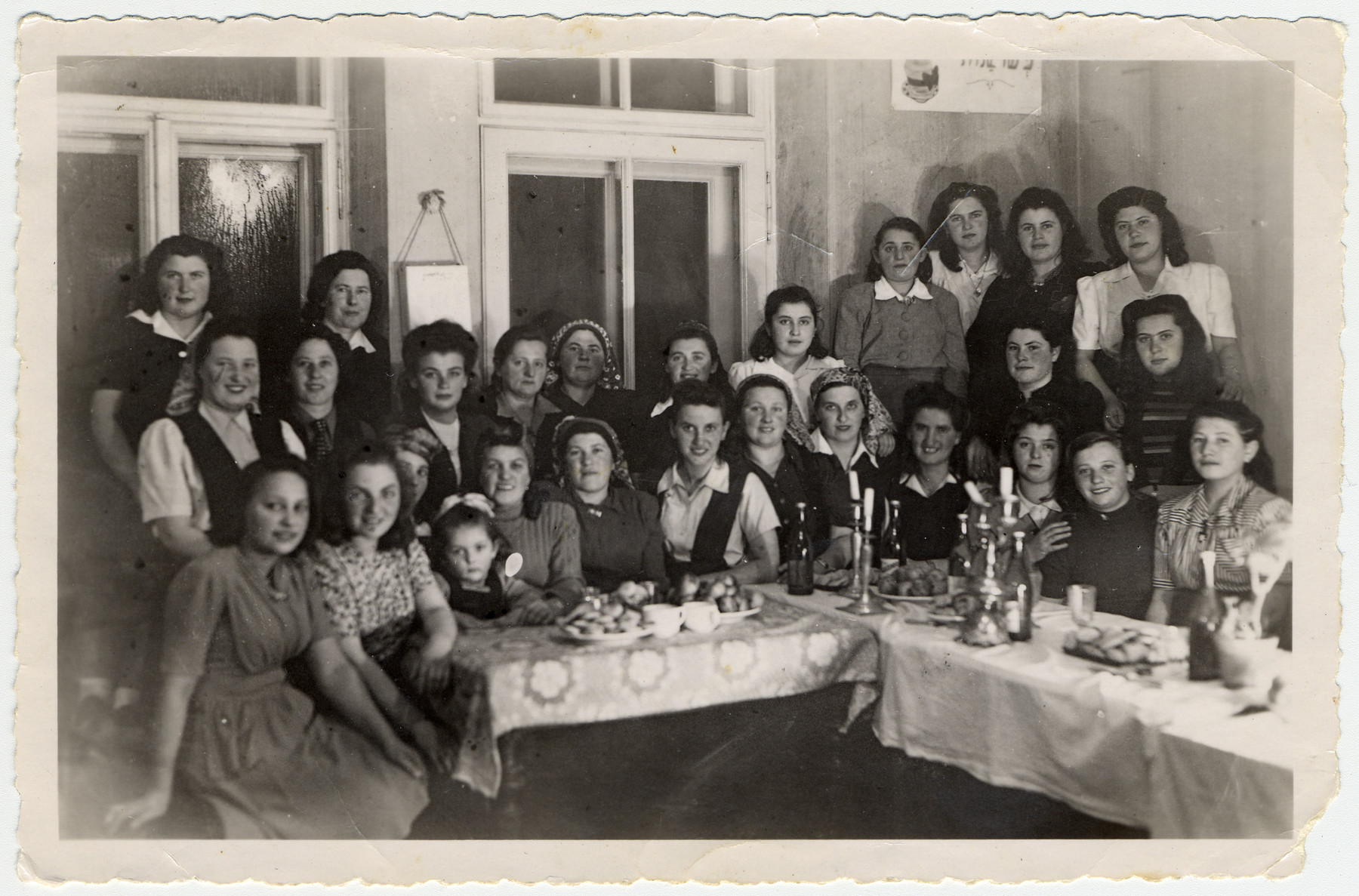 Religious Jewish women gather around a table for a celebration in the Bad Gastein displaced persons' camp.  Among those pictured are Esther and Itka Ass (seated left).