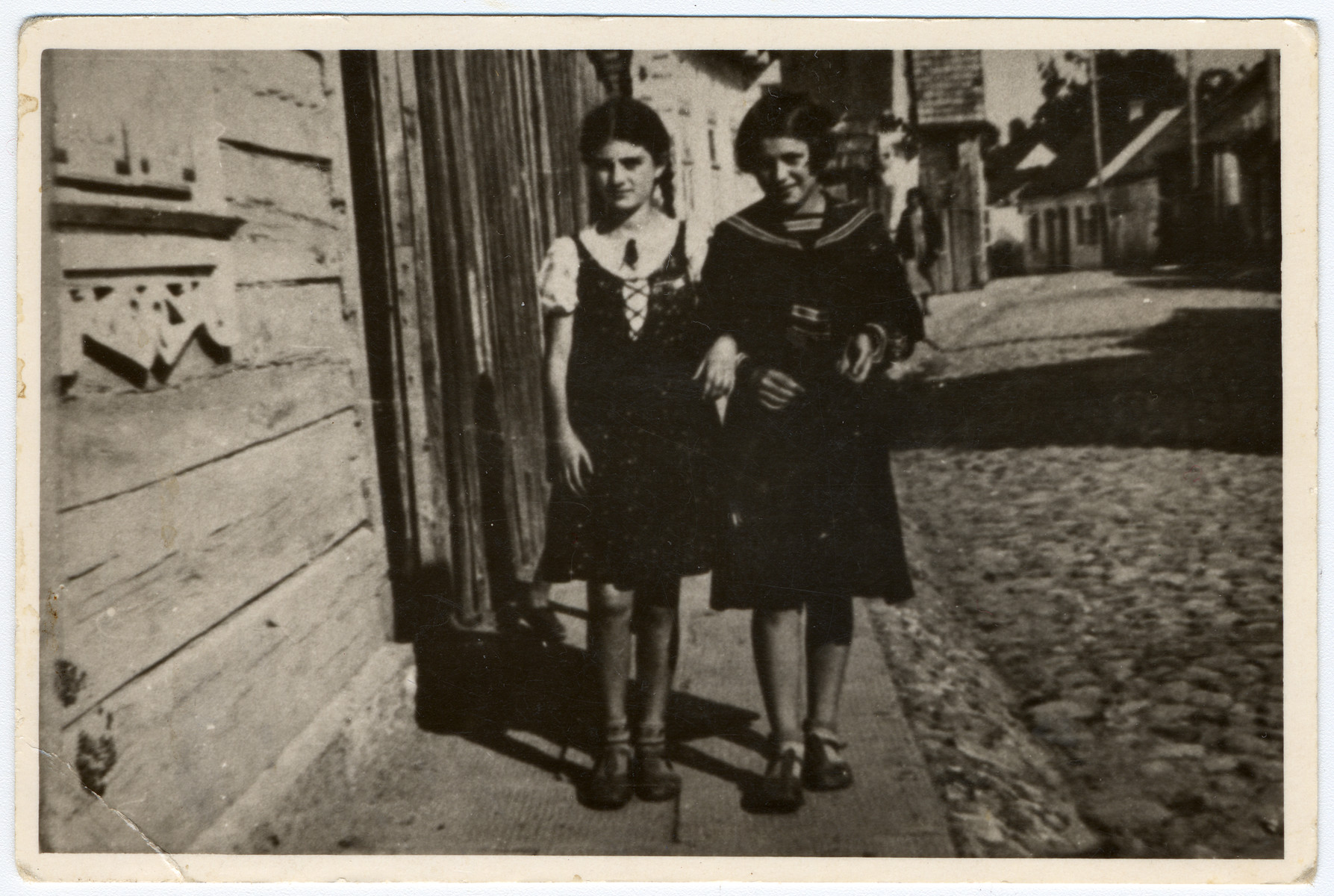 Rachel Ass and her best friend walk down a street in Nowogrodek.  They were both killed following the German invasion of 1941.