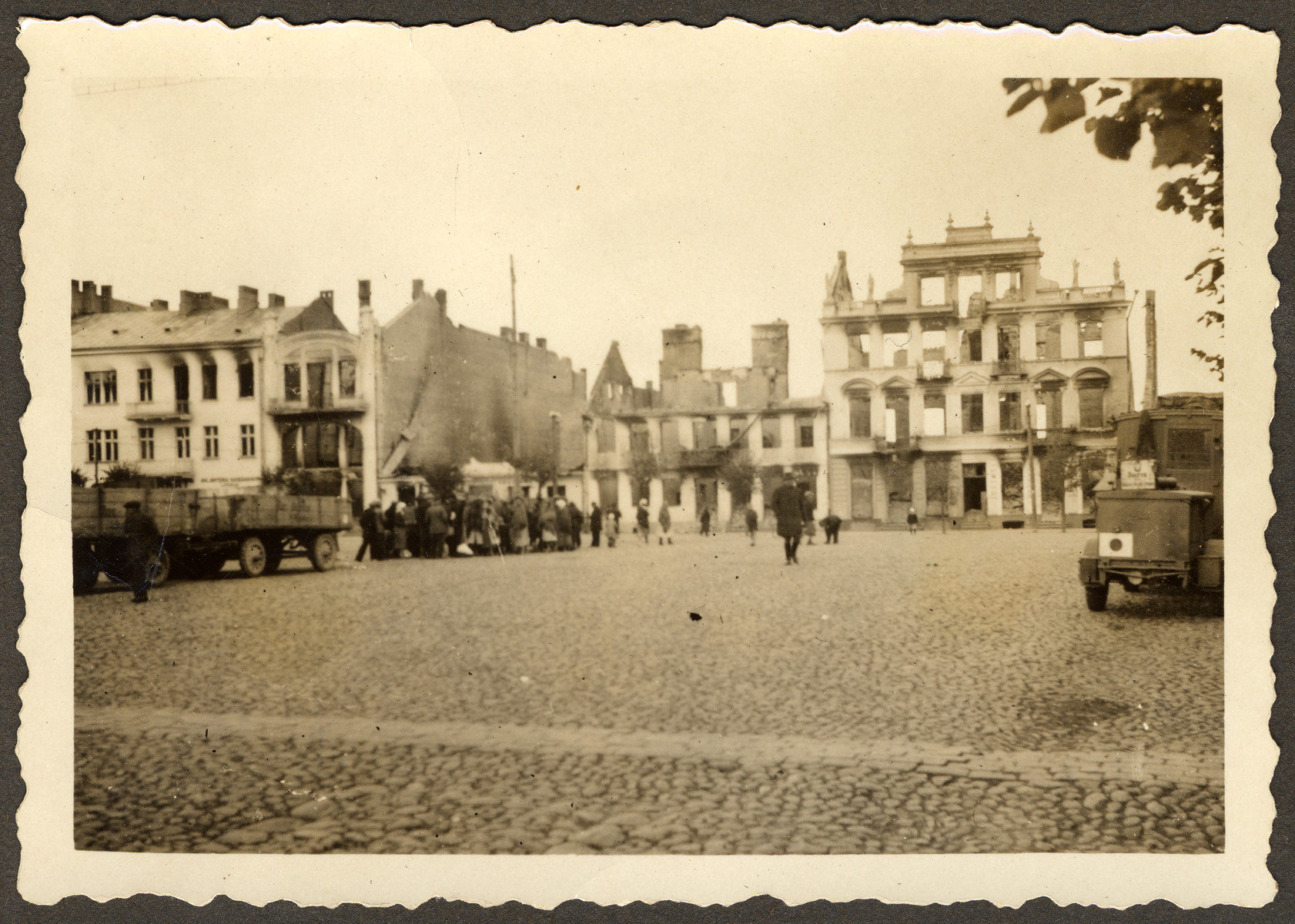 "The ruins of the city square in Mlawa, near Warsaw, Poland. [There is a possible round-up going on in the center, near the large truck on the left hand side of the photo.]  Original German caption reads: ""The city square of Mlawa."""