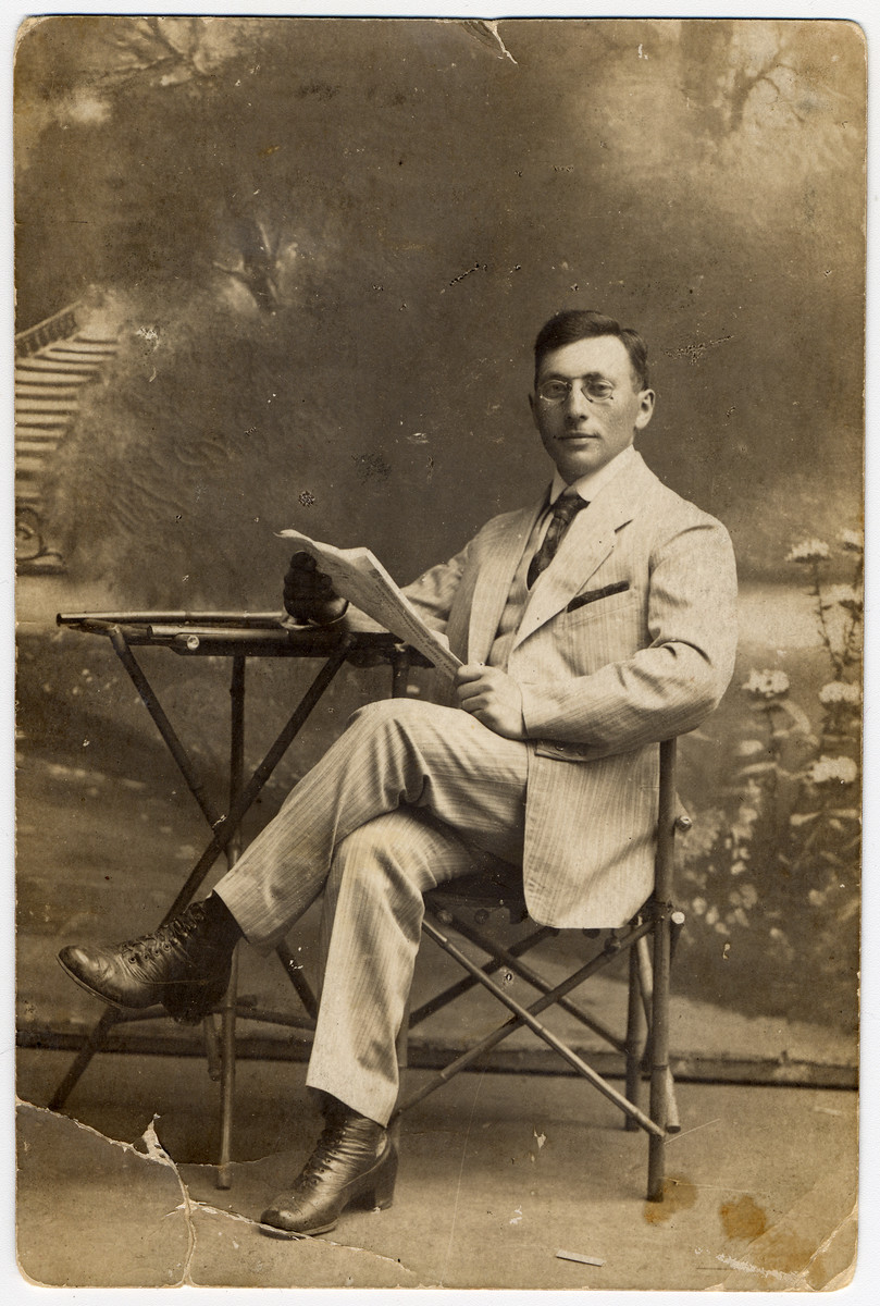 Prewar studio portrait of Yaakov Menachem Ass reading a newspaper.