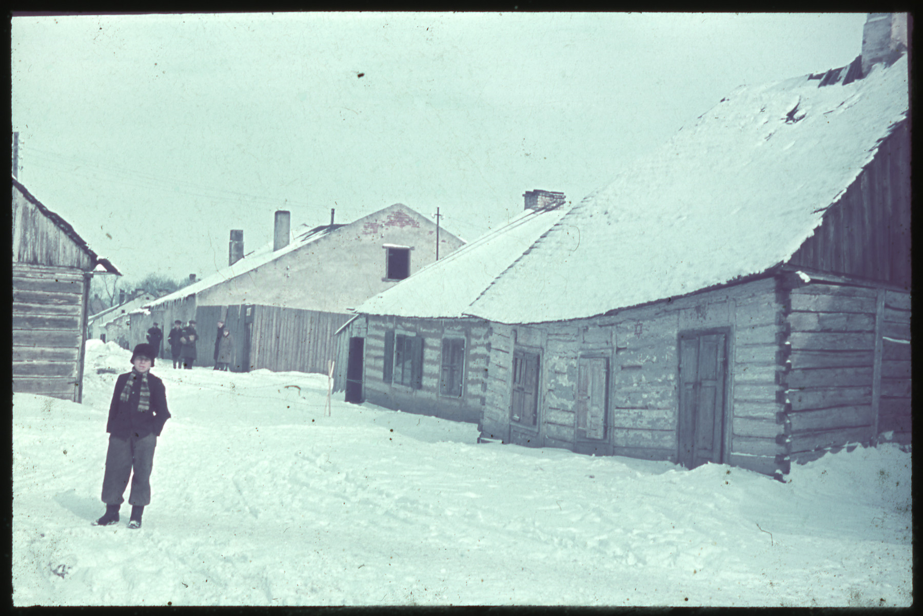 A young boy stands on a snowy road next to a building marked with a Jewish star on its exterior wall while men wearing armbands gather in the background.
