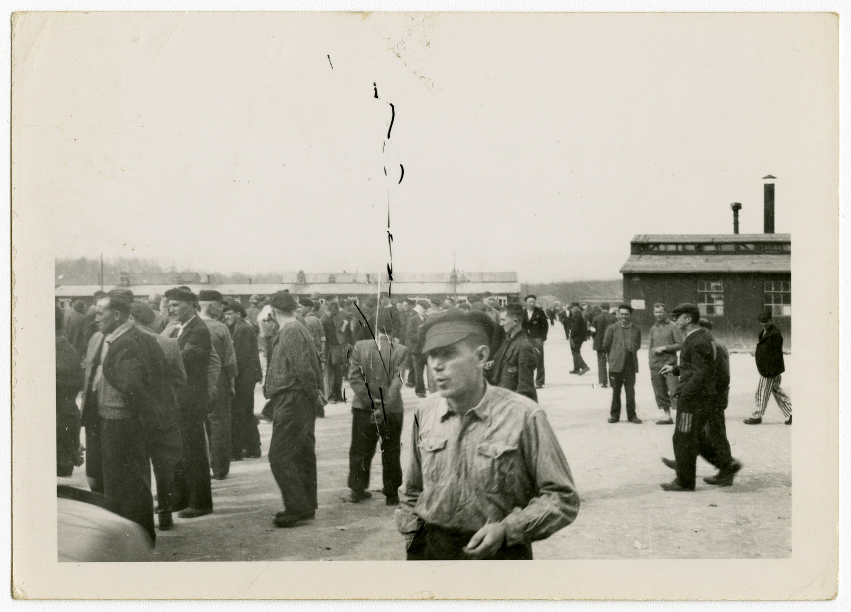 Survivors gather in the open courtyard of [what is probably the Buchenwald concentration camp] after liberation.