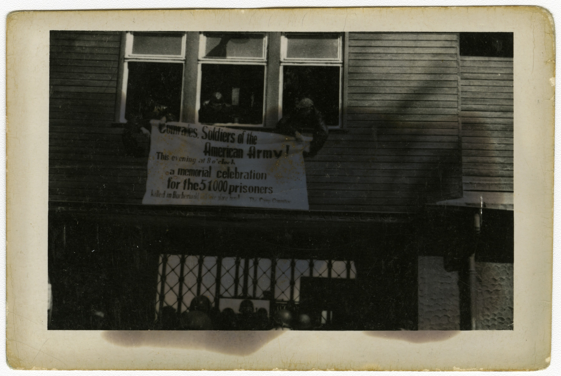 Survivors hang a banner outside the main gate of Buchenwald inviting American soldiers to attend a memorial celebration [sic] for the 51,000 prisoners killed in the Buchenwald concentration camp.