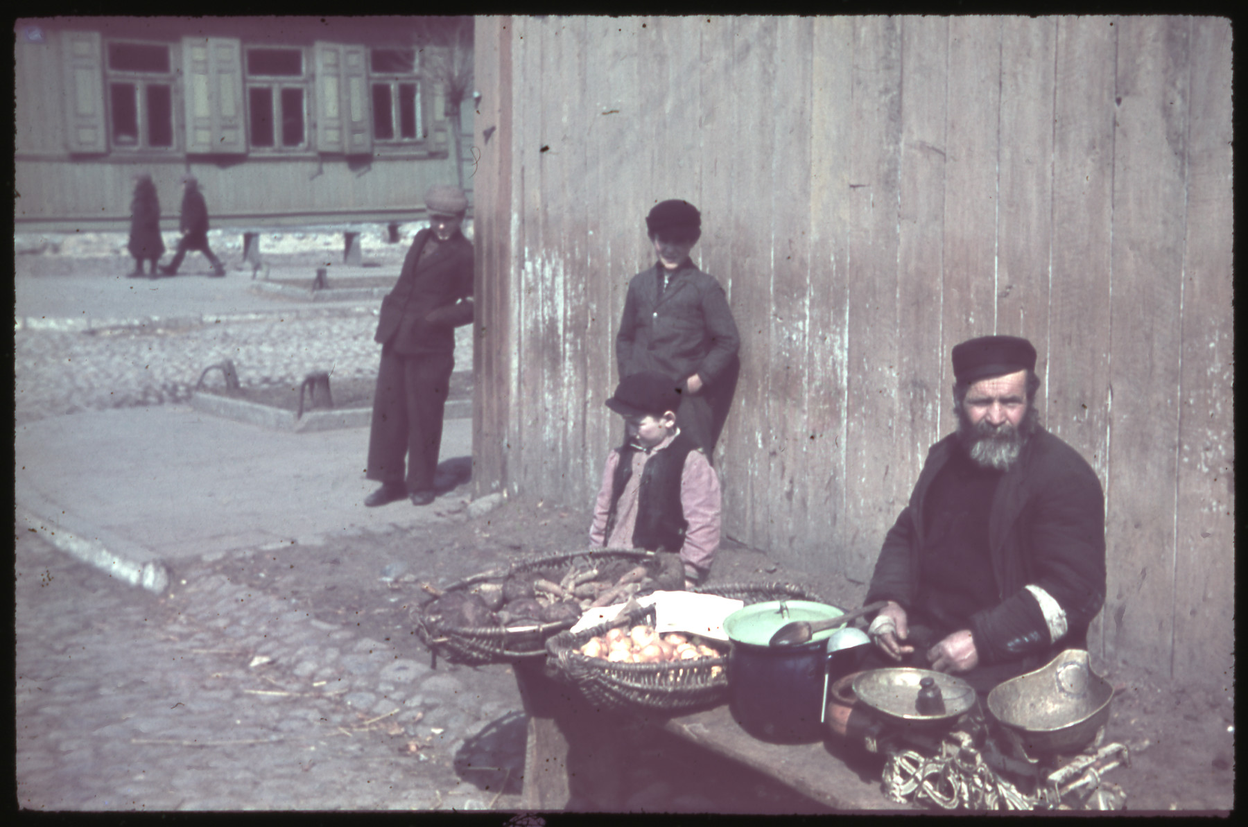 A Jewish man with a beard and armband sells food items on a street corner [perhaps in Kozienice].