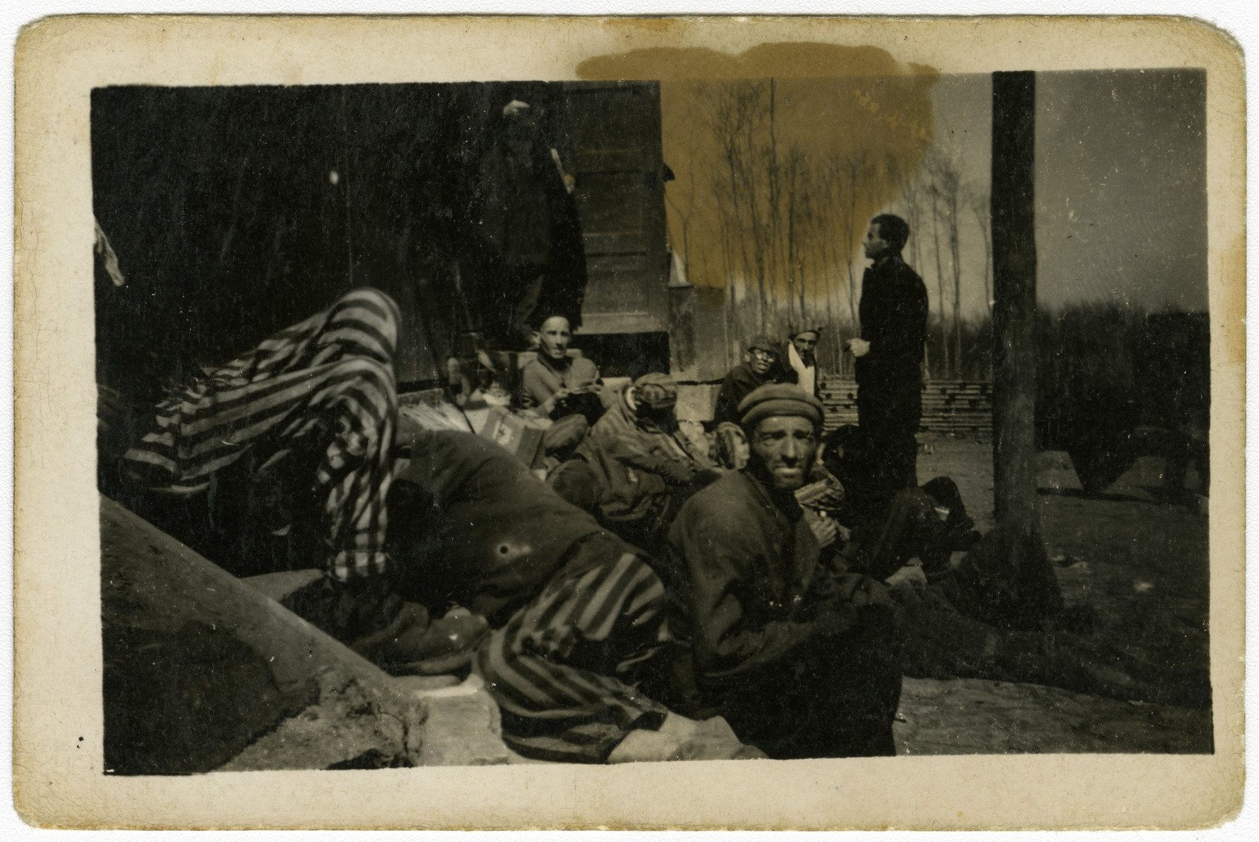 Survivors rest outside a barrack in the Buchenwald concentration camp.