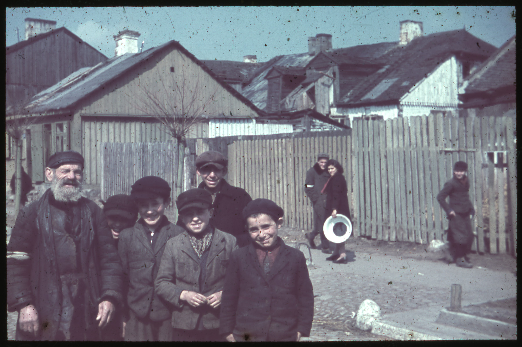 Group portrait of Jewish boys and an elderly man gathered together on a street.