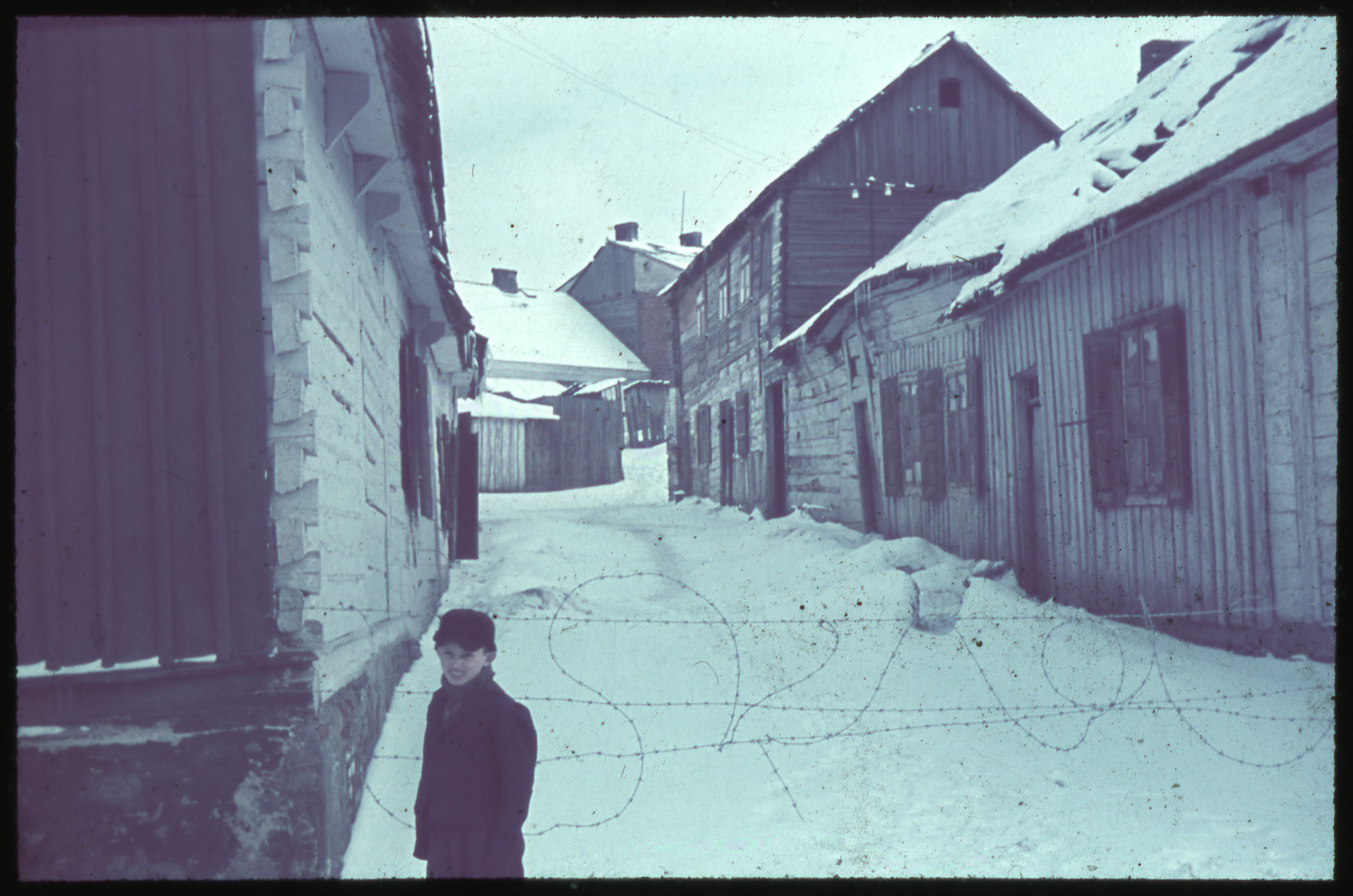 A young boy stands next to a barbed wire fence blocking off a snow-covered road in Kozienice.