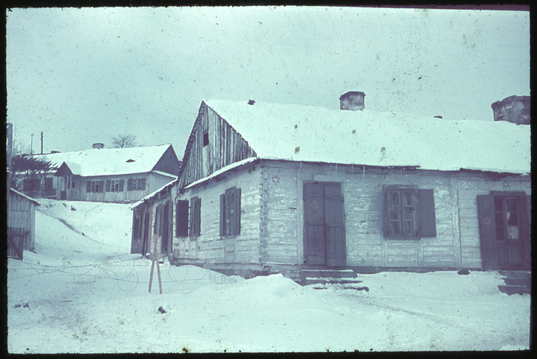 View of a snow covered home [perhaps in Kozienice] marked with Jewish stars on the walls and shutters.