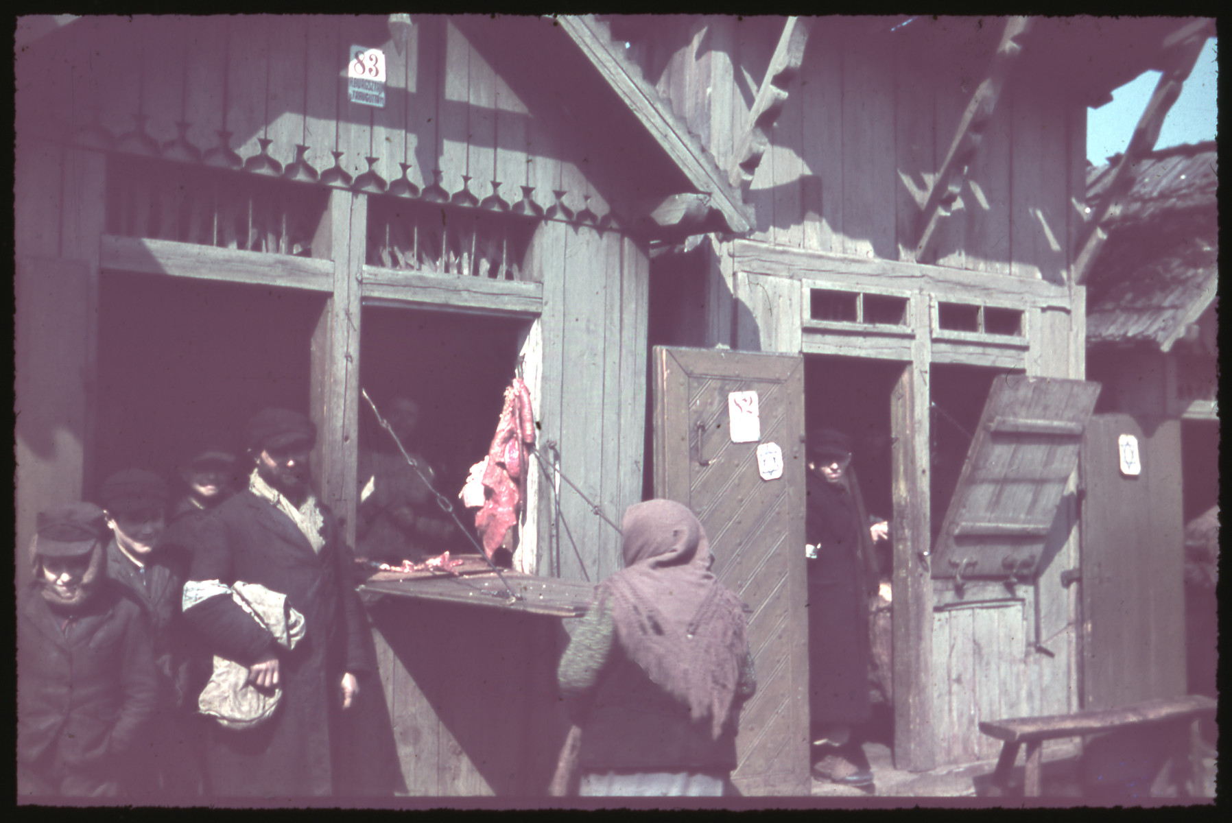 Jews shop in a store marked with a Jewish star on its door [possibly in Kozienice].
