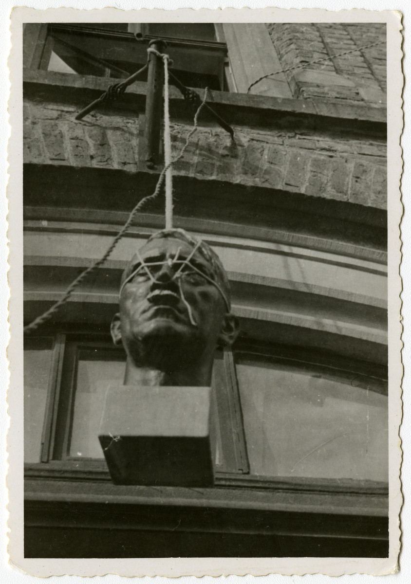 A bust of Adolf Hitler hangs outside of a building in Krofdorf, Germany.   Original caption reads: March 1945  What they should have done with him a long time ago.  Krofdorf, Germany