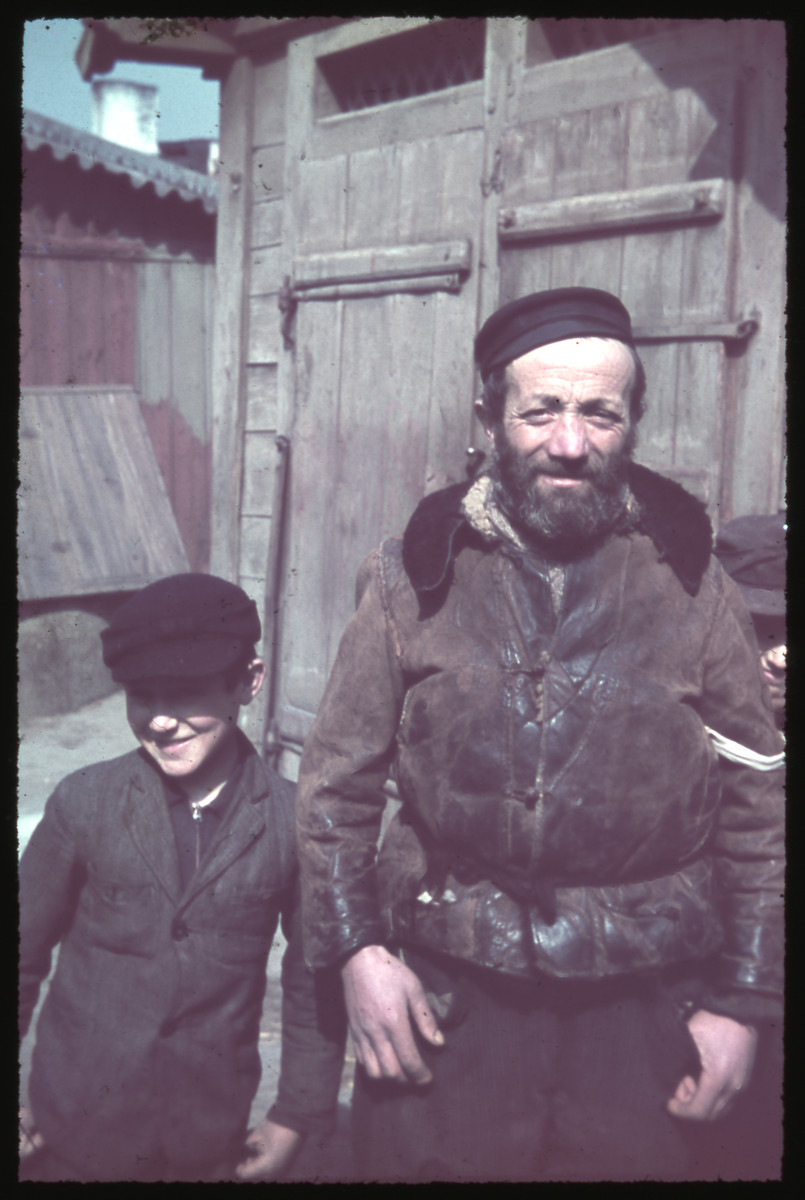 Close-up portrait of a middle-aged man with a beard and armband and a young boy [possibly in Kozienice].