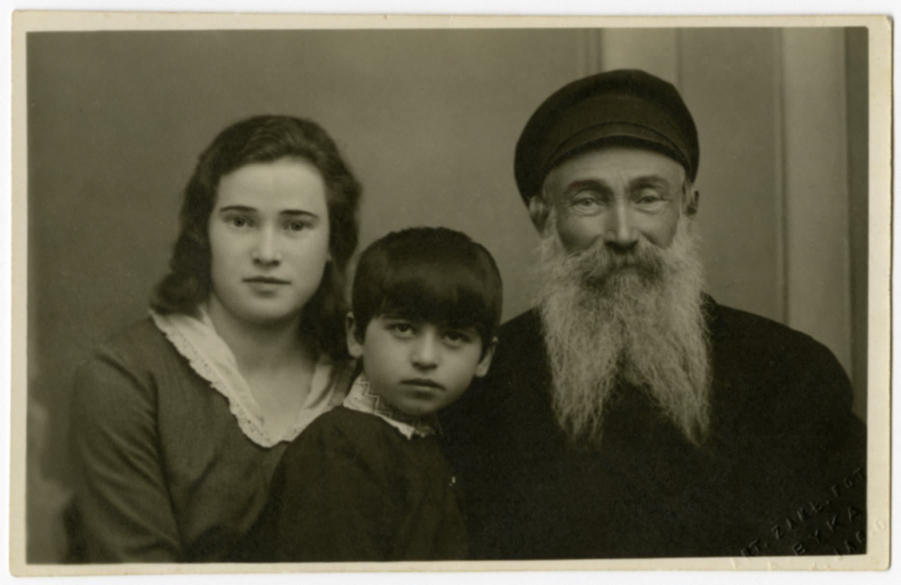 Studio portrait of the Schwartz family.  Pictured aer Brandla Szojchet, a niece and Reuven Schwartz (her father).