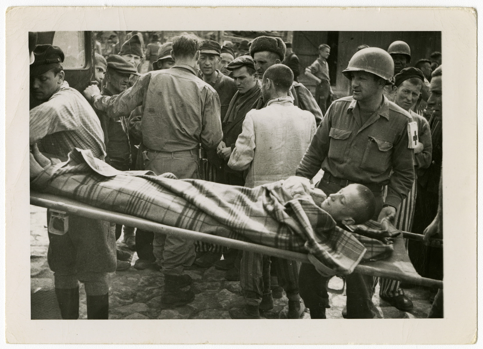 """US Army medics help evacuate ill and starving survivors.  The original caption reads: """"To [sic] starved to walk but taken in an army ambulance to Hospt."""""""