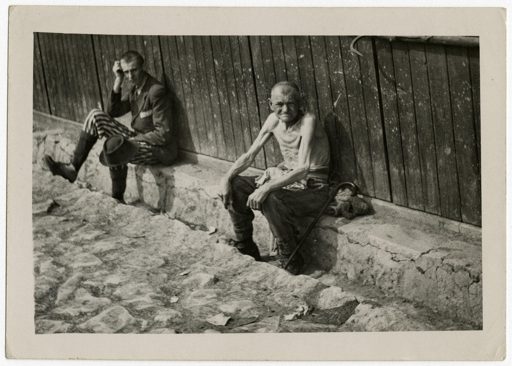"""Two survivors rest against the side of a barrack following liberation.  The original caption reads: """"Free at last."""""""