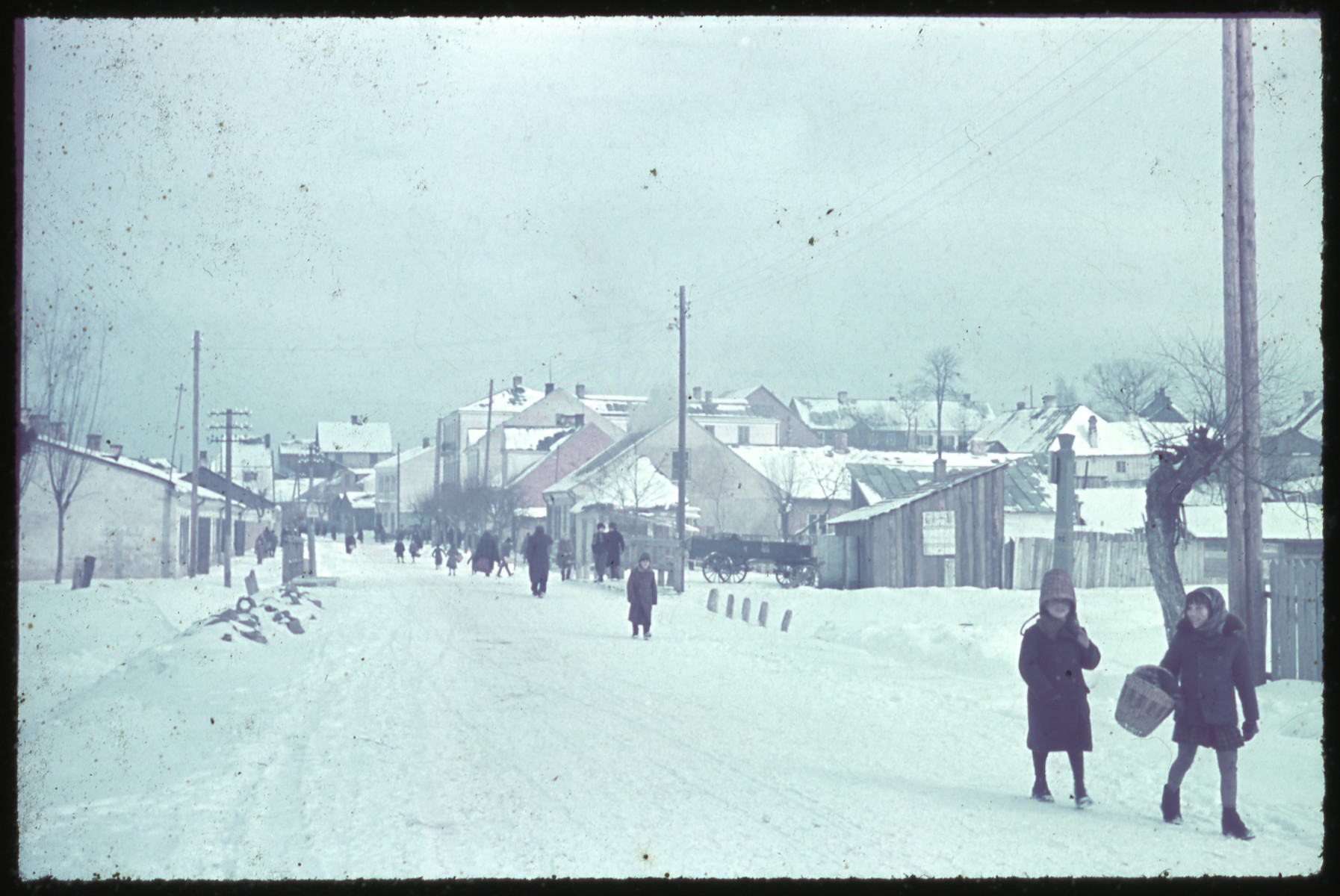 Children walk down a snow-covered road [perhaps in Kozienice].