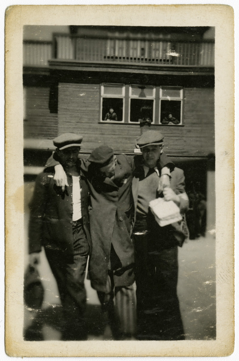 Two survivors help support a third in front of the main entrance to the Buchenwald concentration camp.