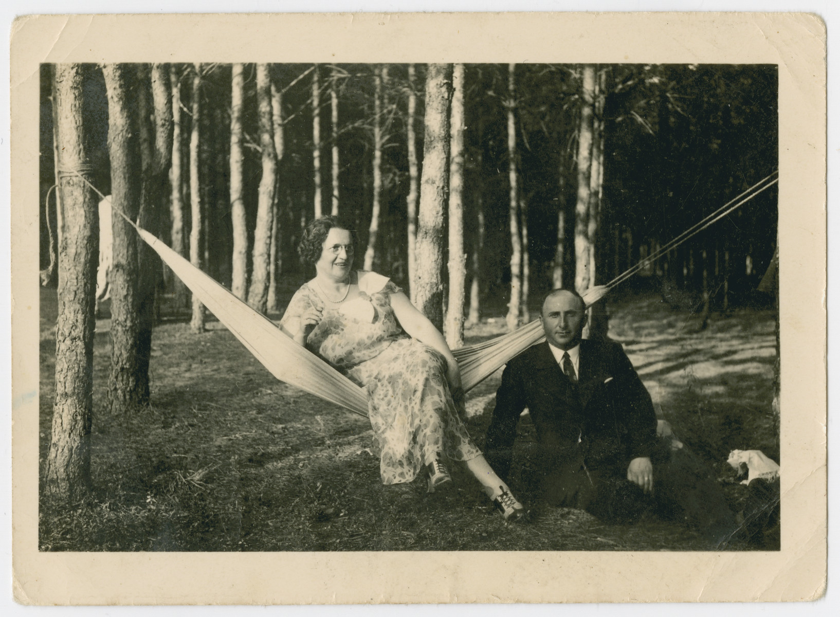 A couple rests on a hammock in prewar Butrimonys.  Part of a collection of photographs depicting Jews from Butrimonys where some 750 Jews were rounded up and murdered by the Einsatzgruppen and Lithuanian collaborators after the invasion of the USSR.