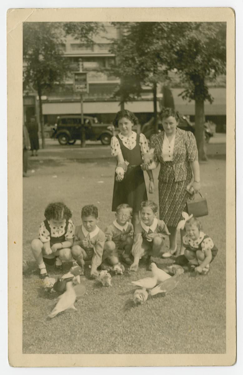 The Spielman and Weiss cousins feed pigeons probably in prewar Holland.  Pictured standing are Regina Weiss and Helen Spielman.  Sitting left to right are Edith Weiss, Henry Weiss, Nathan Spielman, Bernhard Spielman and Hanna Spielman.