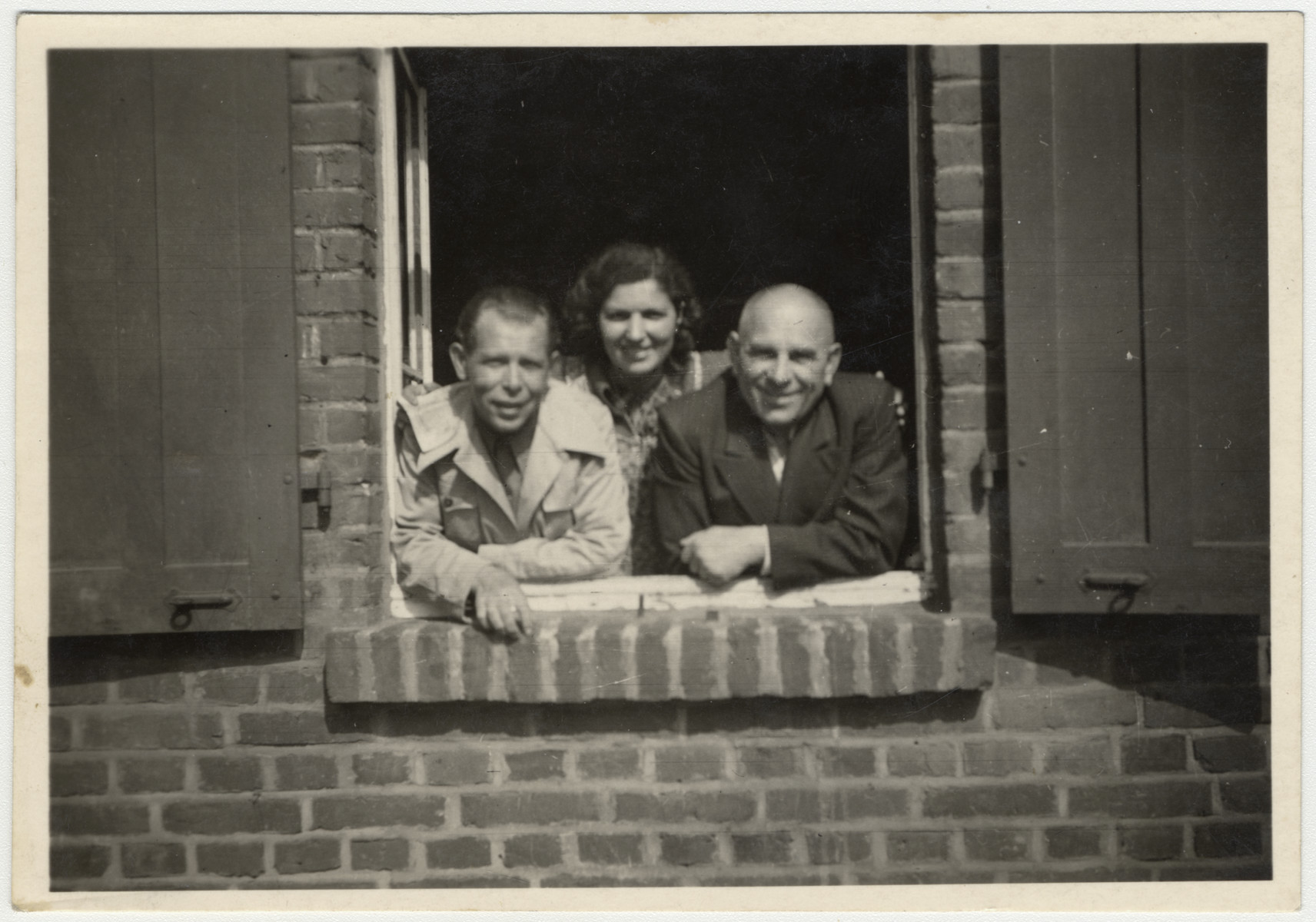Three survivors look out of their window in the Zeilsheim displaced persons' camp.  Pictured are Laibkeh Minuskin, Sonia Minuskin and Moise Mendel.