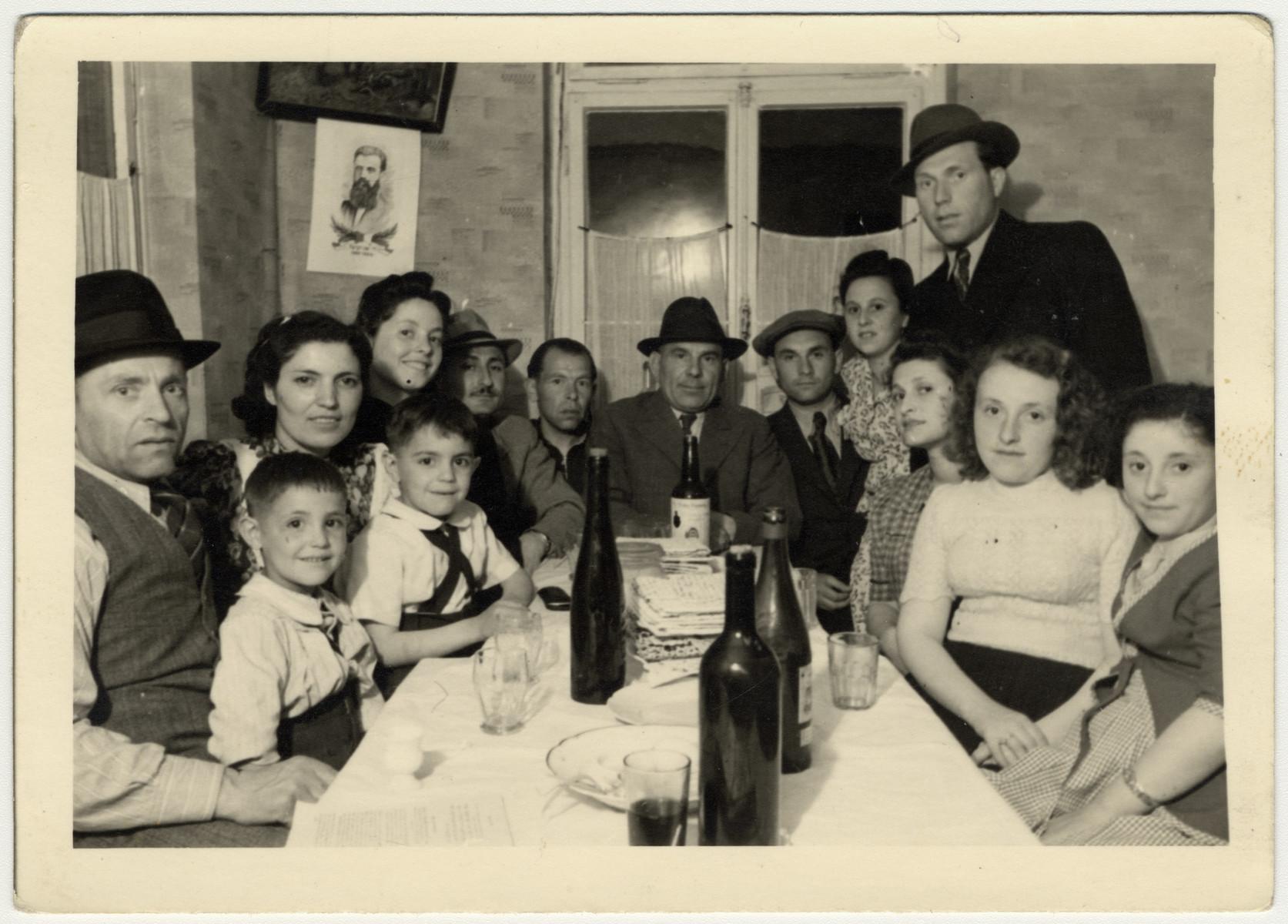 Former Zhetel partisans celebrate their first Passover following their liberation.  Picture from left to right are Shlamke Minuskin, Kalman Minuskin, Sonia Minuskin, Henikel Minuskin, unidentified man and woman, Zavel Modkowski (standing), Sonia Mordkowski