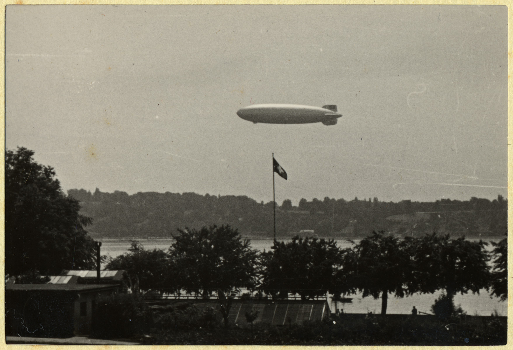 The Hindenburg blimp flies above a Nazi flag.