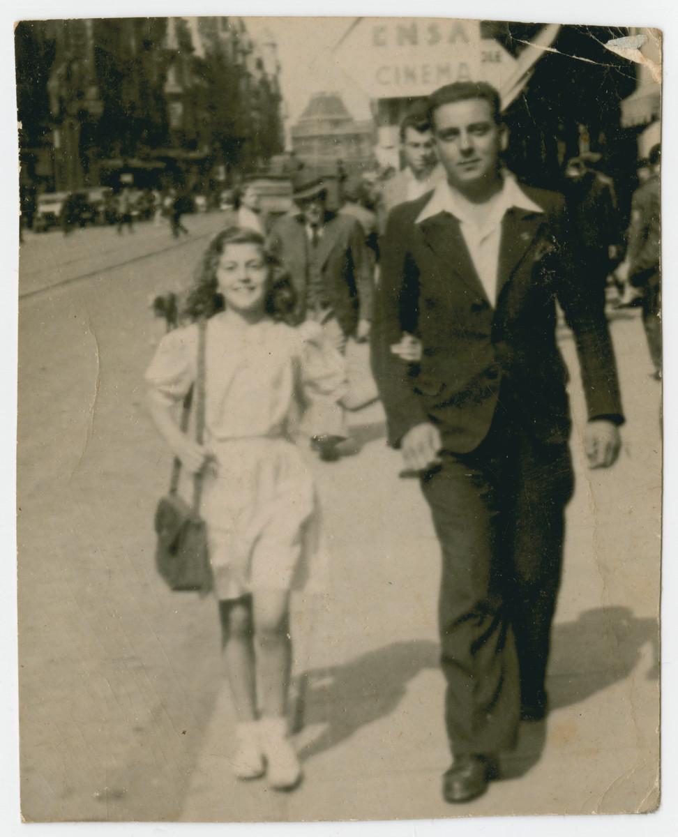 Fanny Fogel walks downn a street in postwar Brussels arm in arm with her father Jacob.