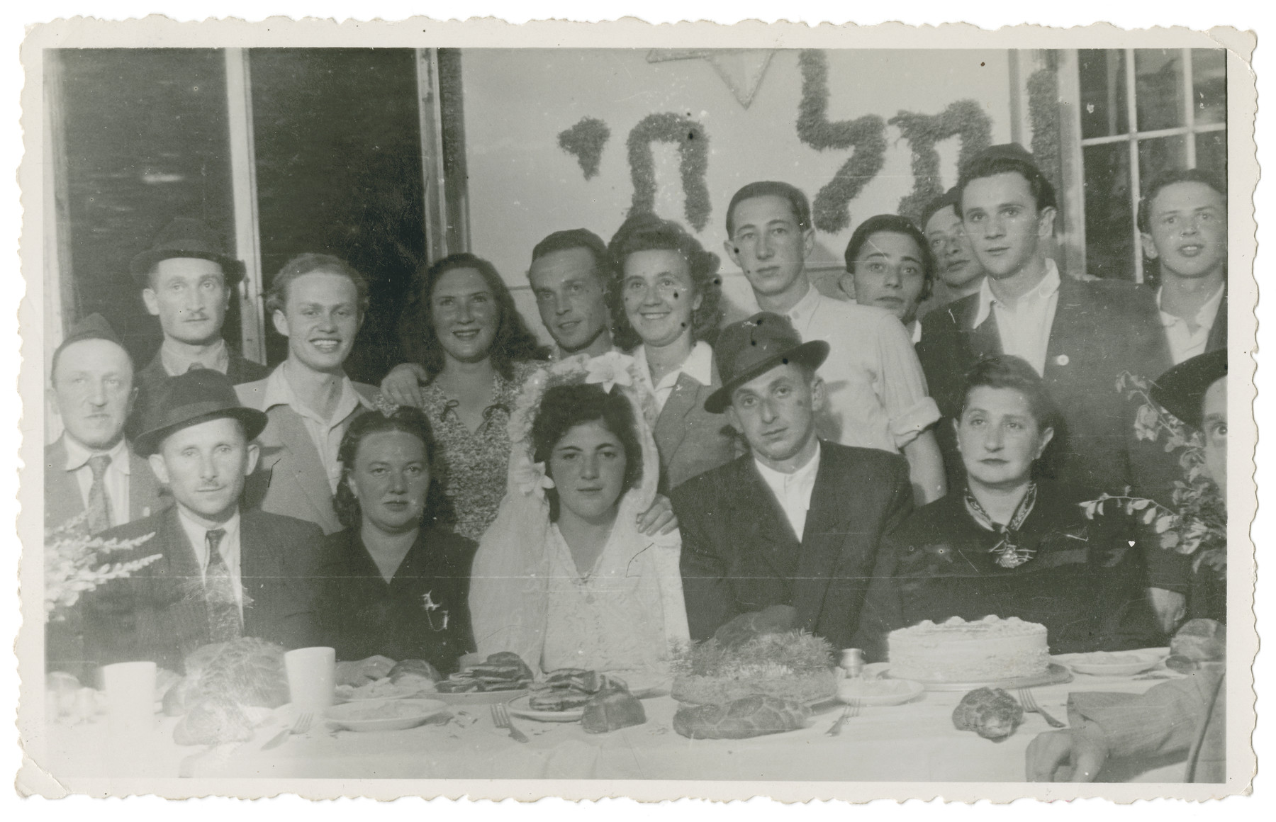 Jewish displaced persons celebrate the marriage of Ruchel Gruenberg and Hershel Kirschner.   Lenke Gruenberg is standing third from the left in the back.  Chaim (Deszo)  Guttman is pictured on the first row to the left of Ruchel with the hat. His wife, Yolanda (Yoli) Rotter Guttman, is directly to the left of Ruchel.   The sign on the back reads Tel Chai, one of the mottoes of the Betar Zionist movement.