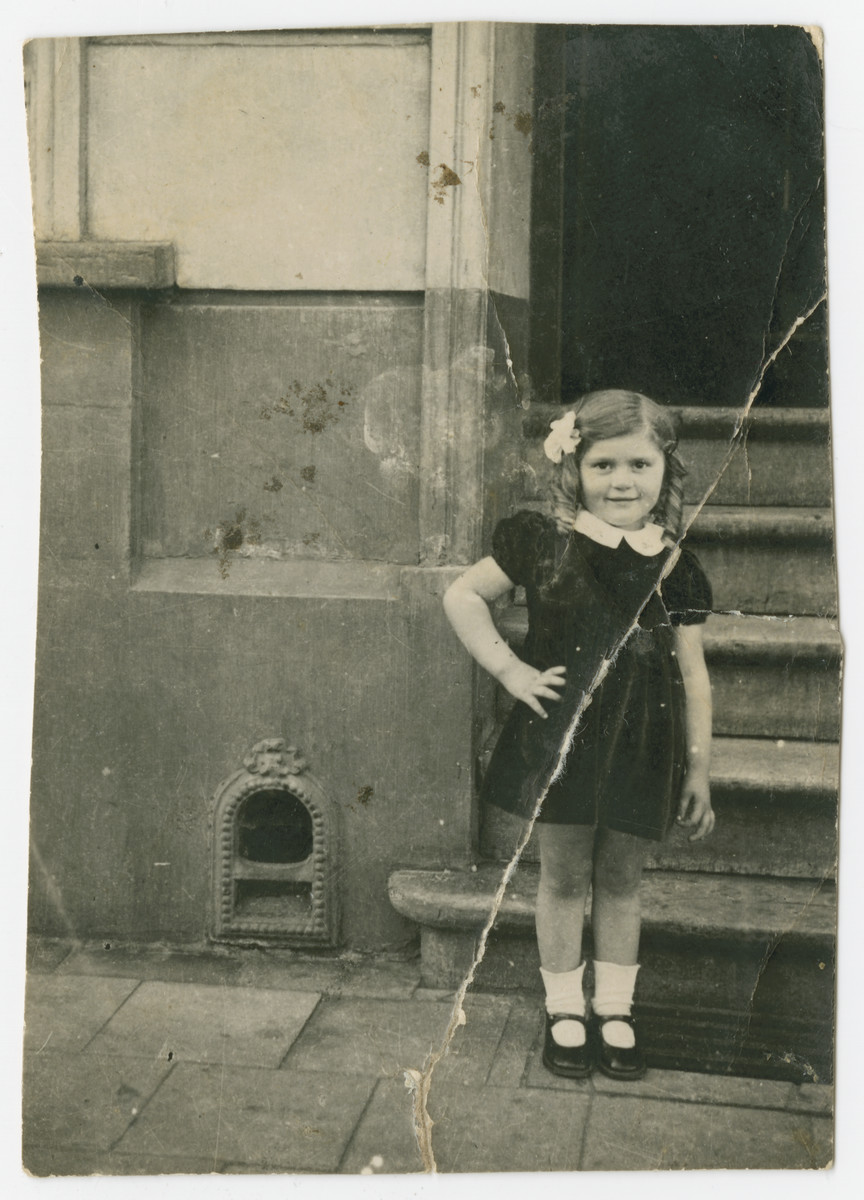 Six-year-old Fanny Fogel stands outside the steps of a building in Antwerp.