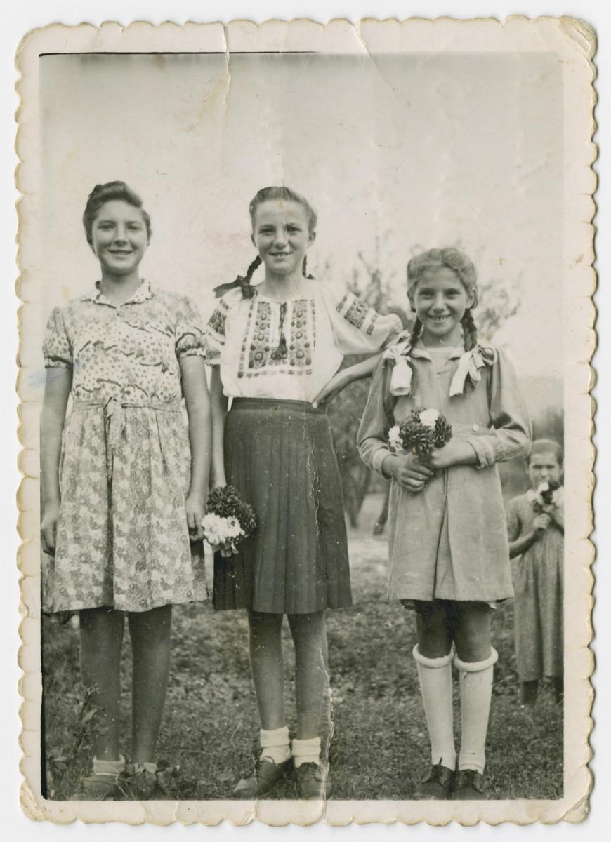 Lenka, Bluma and Malka Gruenberg stand in a field in Cierny Potok holding flowers.