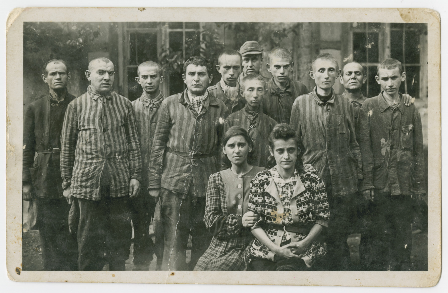 Group portrait of survivors, many still in uniform, in the Dachau concentration camp.  Among those pictured are Zelda Feldlaufer (mother of the donor), and Isak Lips (third from the left.)