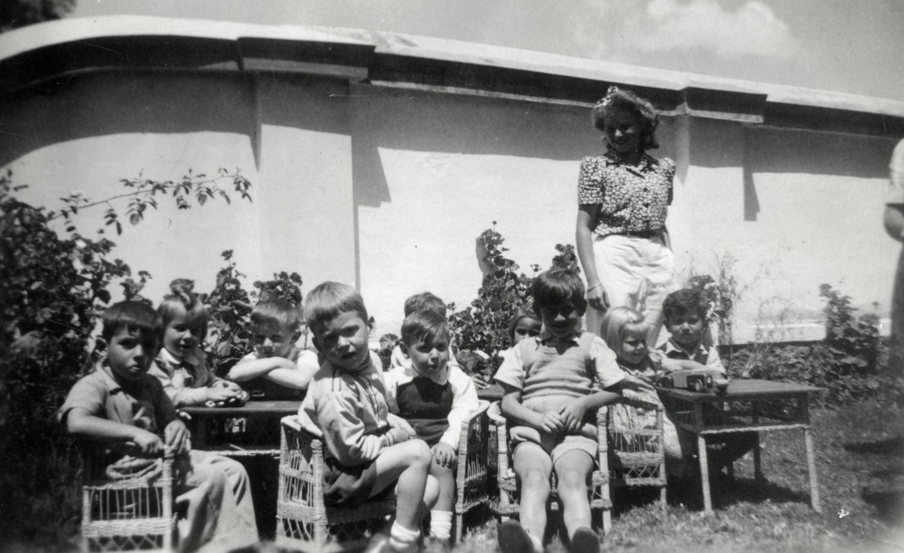 Erika Loebl stands behind the young children in her kindergarten in Quito, Ecuador.