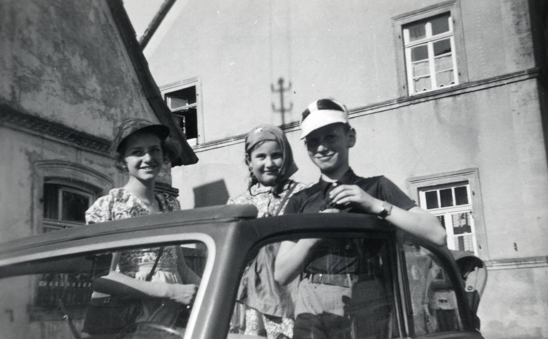 Three German-Jewish children peek out of the open roof of an automobile.  Pictured are Erika and Werner Loebl, and an unidentified younger child standing in the center.