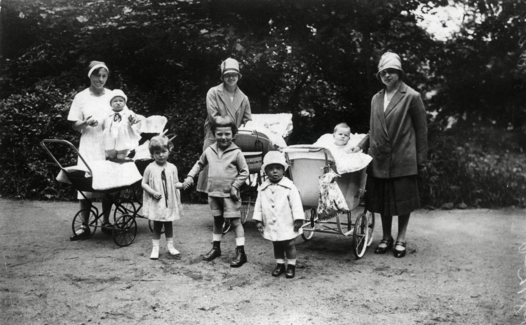 Young German-Jewish children pose with their nannies in Hain Park.  From left to right are Werner Loebl (standing in his carriage), his sister Erika, Herbert, Peter Pausn and Hanna (in her pram).